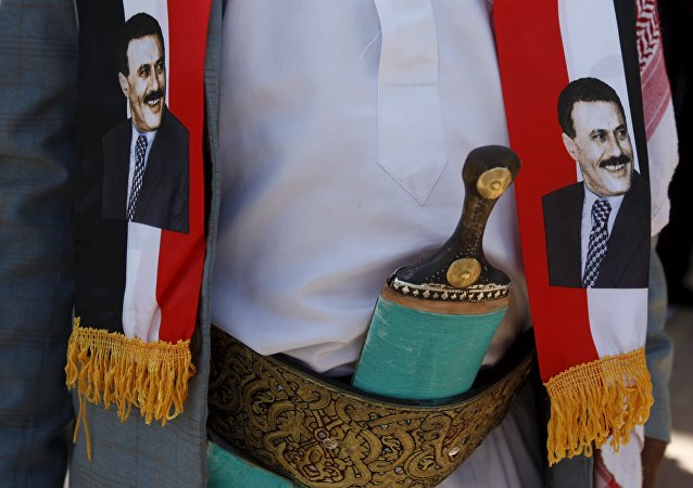 A man wears images of Yemen's former President Ali Abdullah Saleh during a demonstration against the Saudi-led air strikes outside the United Nations offices in Yemen's capital Sanaa October 18, 2015