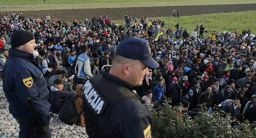 Slovenian police officers watch as migrants walk from Dobova towards a transit camp in Brezice, Slovenia October 21, 2015