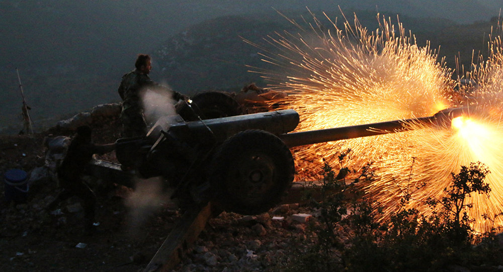 In this photo taken on Saturday, Oct. 10, 2015, Syrian army personnel fire a cannon in Latakia province, about 12 from the border with Turkey in Syria