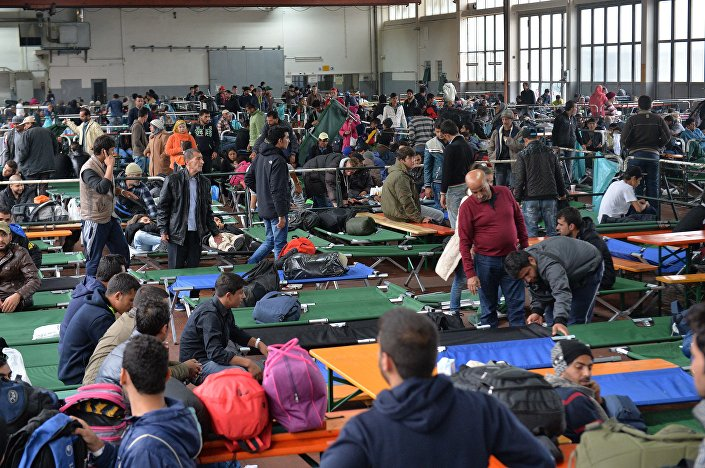 Refugees wait in a crowded migrant registration center in Passau, southern Germany, Thursday, Oct. 8, 2015