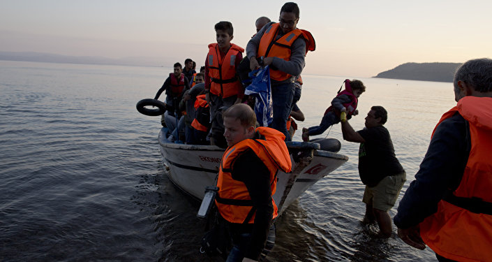 Syrian refugees arrive on a fishing boat from Turkey on the shores of the Greek island of Lesbos , Sunday Sept. 27, 2015.