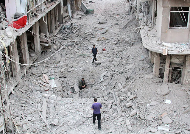 People walk on the rubble of damaged buildings after Syrian military helicopter allegedly droped barrel bombs over the city of Daraya, southwest of the capital Damascus