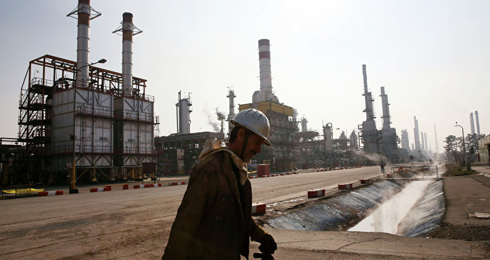 An Iranian oil worker makes his way through Tehran's oil refinery south of the capital Tehran, Iran, Monday, December 22, 2014.