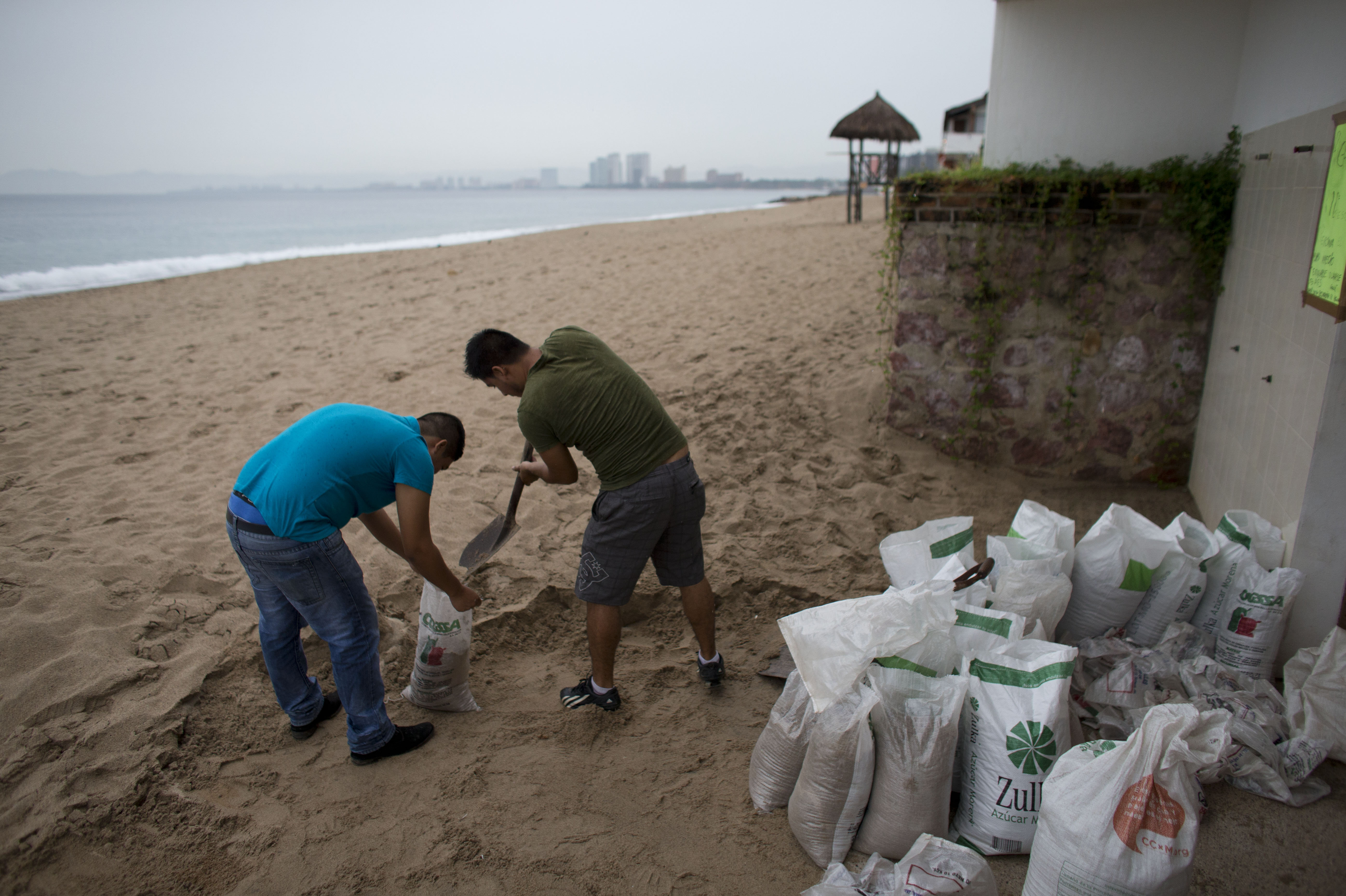 Men fill small bags with sand from the beach as they prepare for the arrival of Hurricane Patricia in Puerto Vallarta.