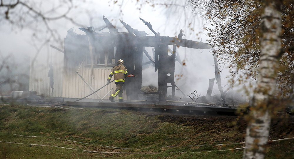 FILE - A Tuesday, Oct. 20, 2015 photo from files showing a firefighter working in the smoking remains of an accommodation home for asylum seekers near Munkedal in western Sweden