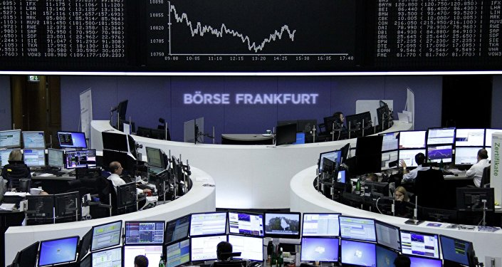 Traders are pictured at their desks in front of the DAX board at the stock exchange in Frankfurt, Germany, October 29, 2015