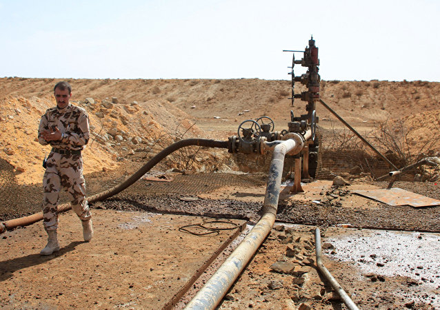 A member of the Syrian government forces walks next to a well at Jazel oil field, near the ancient city of Palmyra in the east of Homs province after they retook the area from Islamic State (IS) group fighters on March 9, 2015