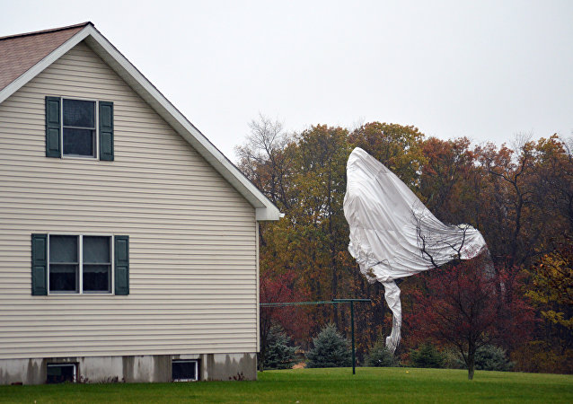 Part of an unmanned Army surveillance blimp hangs off a group of trees after crash landing near Muncy, Pa.