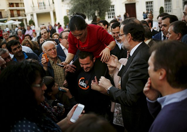 Prime Minister Mariano Rajoy (R) helps a woman to get down from the shoulders of a man before an electoral rally to open the electoral pre-campaign of the People's Party (PP) for the Spanish general elections, in Cabra, southern Spain, October 29, 2015