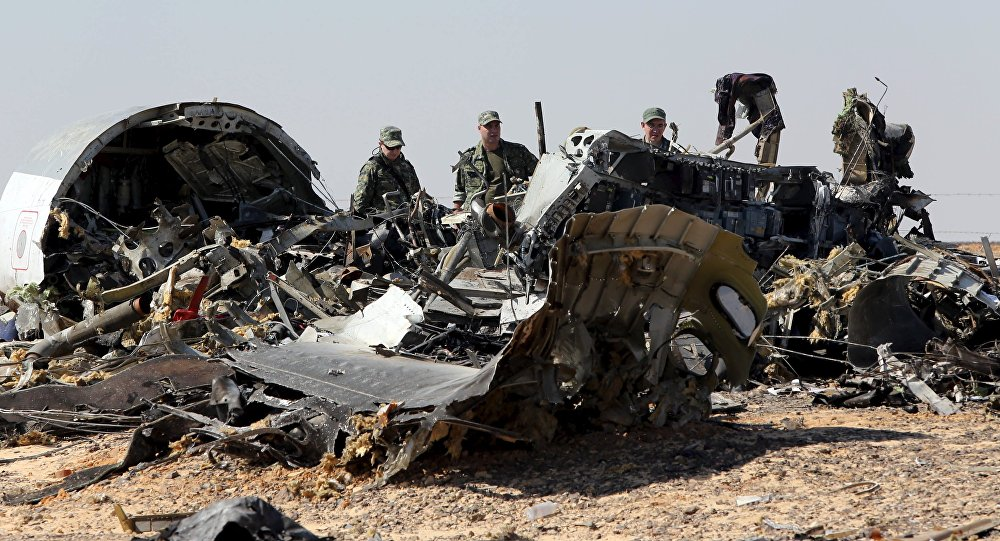 Military investigators from Russia stand near the debris of a Russian airliner at the site of its crash at the Hassana area in Arish city, north Egypt, November 1, 2015