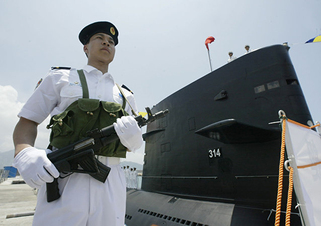 A member of the PLA Navy Task group guards a Chinese PLA Naval submarine berthed in Hong Kong waters 30 April 2004