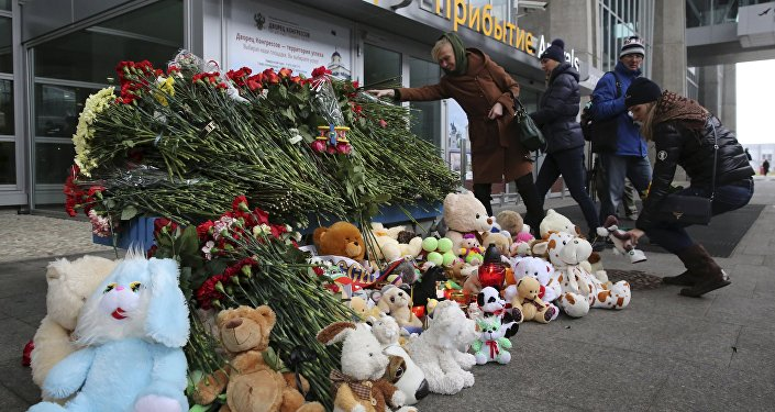 People lay toys and flowers for victims of a Russian airliner which crashed in Egypt, outside Pulkovo airport in St. Petersburg, Russia November 1, 2015