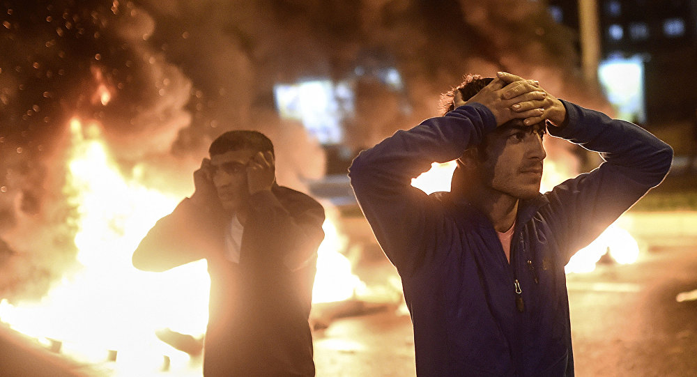 People react as smoke billows from burning pallets set on fire during clashes between Turkish riot policemen and Kurdish protesters in the southeastern city of Diyarbakir on November 1, 2015 after first results of the Turkish general election showed a clear victory to the Justice and Development Party (AKP). Turkish police fired tear gas and water cannon at Kurds who were protesting after the election appeared to deliver a clear victory to AKP, an AFP photographer said. Latest results say the pro-Kurdish People's Democratic Party (HDP) won slightly over 10 percent of the vote, just enough to scrape into parliament.