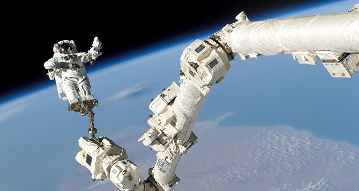 Astronaut Stephen K. Robinson, STS-114 mission specialist, anchored to a foot restraint on the International Space Station's Canadarm2, participates in the mission's third session of extravehicular activity (EVA) August 3, 2005
