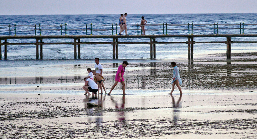 Tourists walk by the beach at the Egyptian Red Sea resort of Sharm el-Sheikh on November 2, 2015.