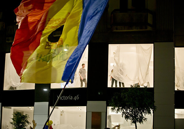 People re-decorate a shop as Romanians waving a flag fill the Calea Victoriei, a main avenue of the Romanian capital, during a large protest in Bucharest, Romania, Tuesday, Nov. 3, 2015.