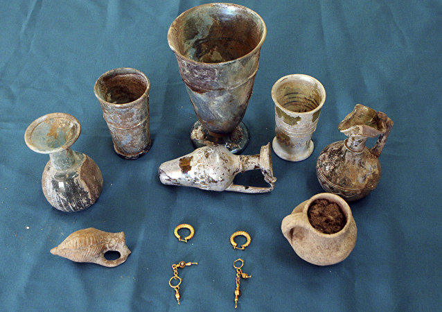 Glassware, potteries and golden earrings that have been recently unearthed by Syrian archeologists in a cemetery in Hina town. (File)