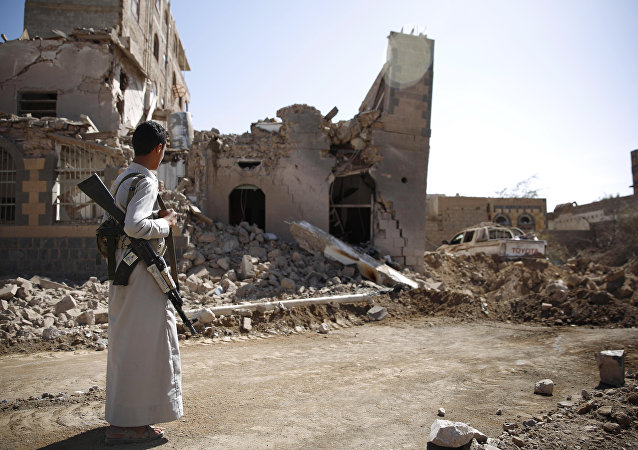 A Shiite fighter, known as a Houthi, look at a house destroyed by Saudi-led airstrikes in Sanaa, Yemen (File)