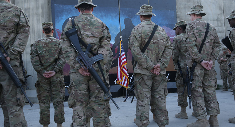 U.S. service members stand in front of a U.S. flag during a ceremony on the thirteenth anniversary of the 9/11 terrorist attacks in front of the World Trade Center Memorial at Bagram Airfield, Afghanistan, Thursday, Sept. 11, 2014