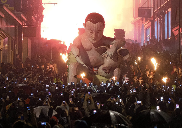 Spectators use smartphones to photograph an effigy depicting Britain's Prime Minister David Cameron as it is paraded through the streets of Lewes in Sussex, southern England on November 5, 2015, during the traditional Bonfire Night celebrations.