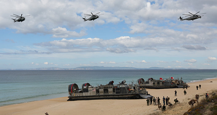 FILE - In this Oct. 20, 2015 file photo, U.S. navy helicopters fly over U.S. Navy hovercraft during the NATO Trident Juncture exercise 2015 at Raposa Media beach in Pinheiro da Cruz, south of Lisbon