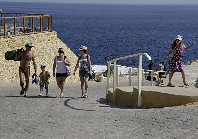 Tourists leave the beach at a resort where many stranded tourists are waiting for evacuation, in Sharm el-Sheikh, south Sinai, Egypt, Saturday, Nov. 7, 2015
