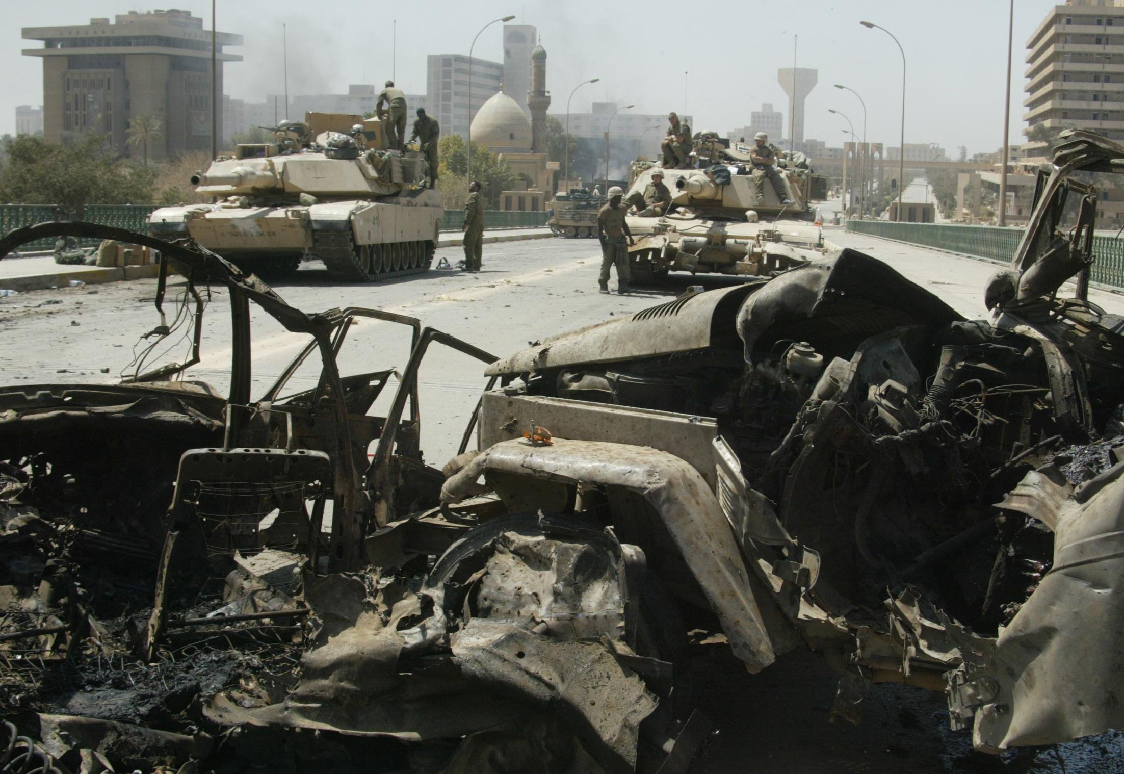 US marines sit on their tanks behind the wreckage of destroyed cars on al-Jumhuriya bridge in Baghdad 11 April 2003