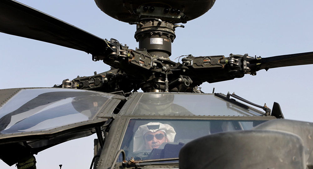 An Emirati man checks out an Apache helicopter during the opening of the Dubai Airshow in United Arab Emirates, Sunday, Nov. 8, 2015