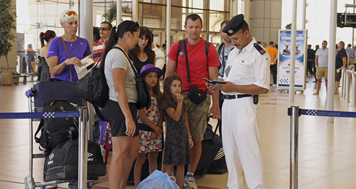 British tourists have their documents checked by Egyptian police as they prepare to be evacuated from Sharm el-Sheikh airport, south Sinai, Egypt, Friday, Nov. 6, 2015