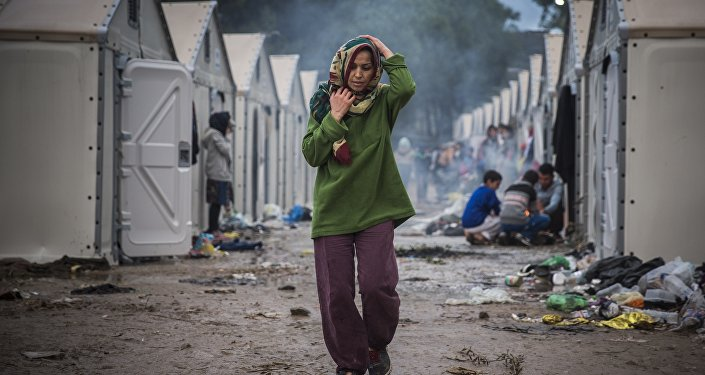A woman walks inside the Moria camp for migrants and refugees on the northeastern Greek island of Lesbos, Saturday, Oct. 24, 2015