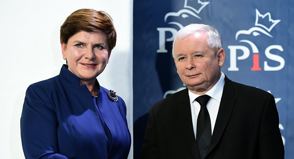 Jaroslaw Kaczynski (R), the leader of the conservative Law and Justice (PiS) party, shakes hands with designated prime minister Beata Szydlo after she announced members of her new cabinet on November 9, 2015 in Warsaw