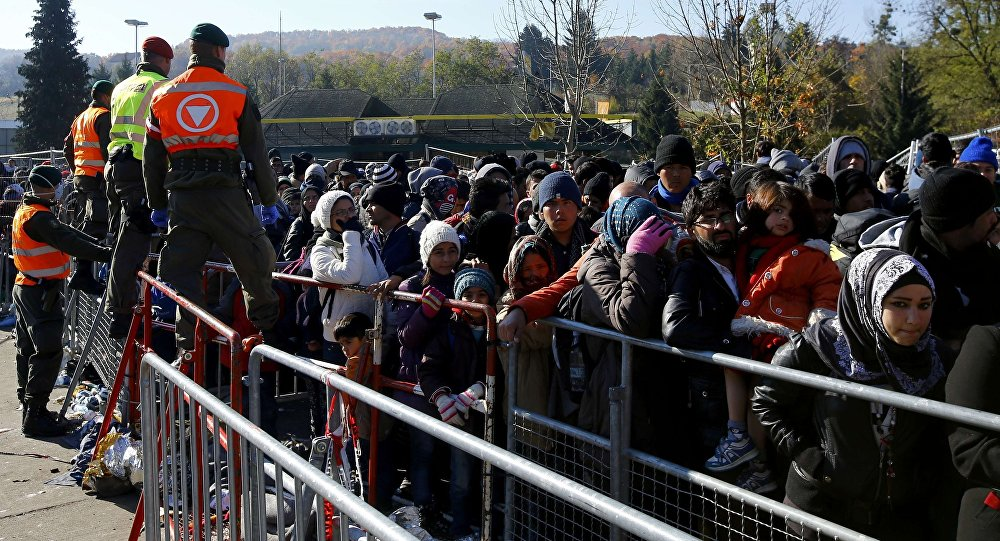 Austrian army soldiers observe migrants as they wait to cross the border from the village of Sentilj, Slovenia into Spielfeld in Austria, November 2, 2015