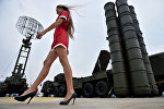 A woman walks near Russia's air defence system S-400 Triumf launch vehicles