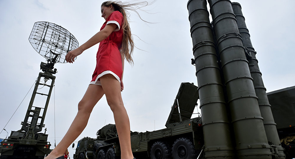 A woman walks near Russia's air defence system S-400 Triumf launch vehicles at the military exhibition