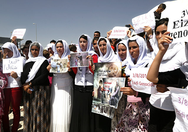 Yazidi Kurdish women hold posters during a protest against the Islamic State group's invasion on Sinjar city one year ago, in Dohuk, northern Iraq.