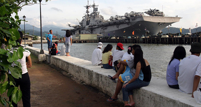 People stand near the docked amphibious assault ship USS Essex at Subic Bay, Philippines.
