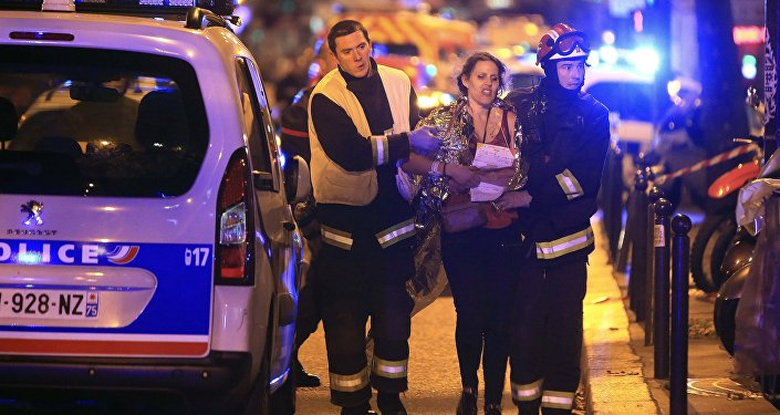 Rescue workers help a woman after a shooting, outside the Bataclan theater in Paris,November 13,2015