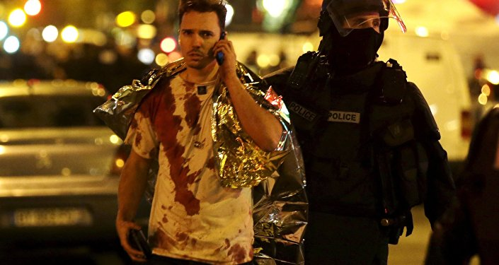 French policeman assists a blood-covered victim near the Bataclan concert hall following attacks in Paris, France, November 14, 2015