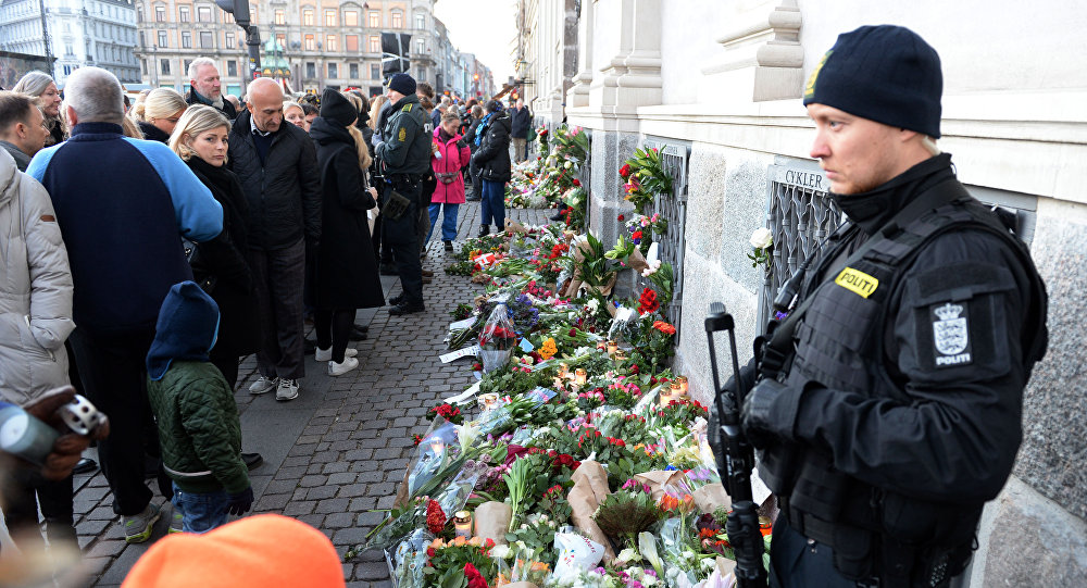 People place flowers in front of the French Embassy in Copenhagen, Denmark, Saturday, Nov. 14, 2015, as people gather with condolences for the victims of Friday's attacks in Paris