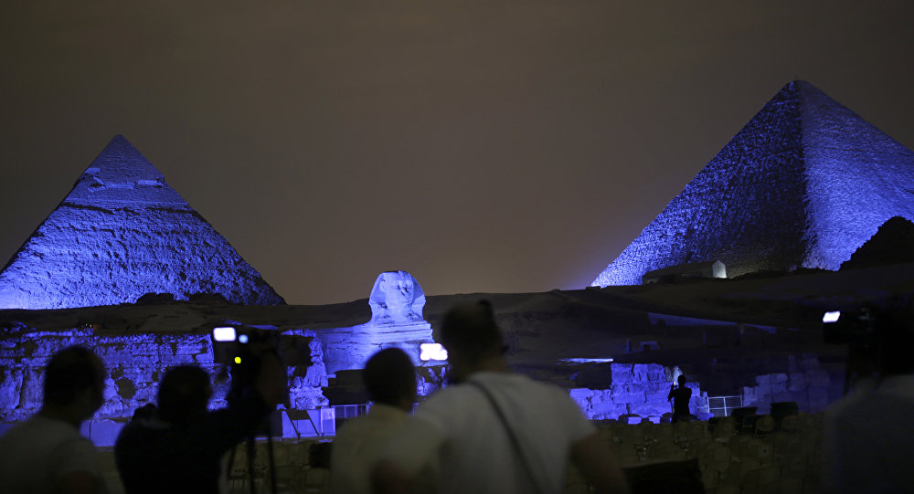 Egyptians watch the historical site of the Giza Pyramids as they are illuminated with blue light, as part of the celebration of the 70th anniversary of the United Nations, in Giza, just outside Cairo, Egypt, Saturday, Oct. 24, 2015