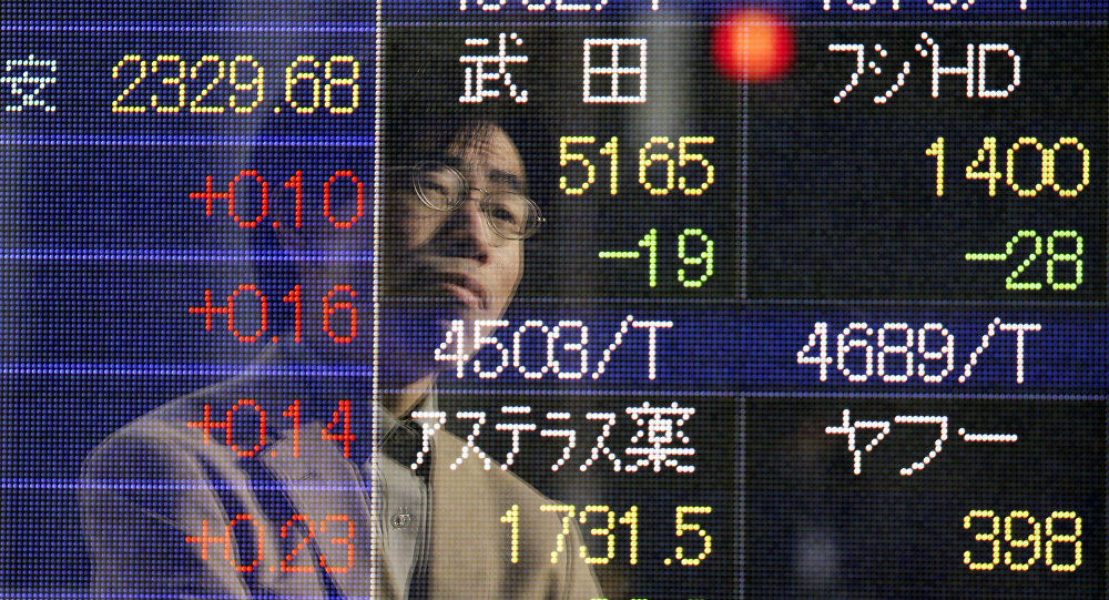 A man is reflected on an electronic board of a securities firm in Tokyo Friday, Jan. 16, 2015.
