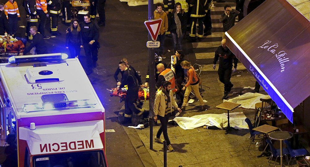 French fire brigade members aid an injured individual near the Bataclan concert hall following fatal shootings in Paris, France, November 13, 2015.