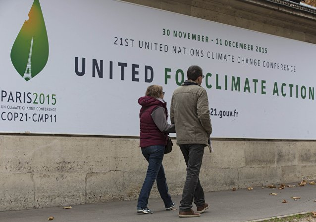 Pedestrians walk in front of posters for the COP 21 World Climate Summit in Paris, France,