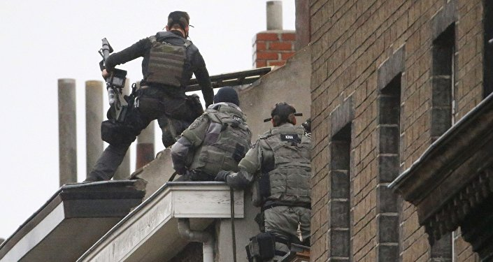 Belgian special forces police climb high on an apartment block during a raid, in search of suspected muslim fundamentalists linked to the deadly attacks in Paris, in the Brussels suburb of Molenbeek, November 16. 2015