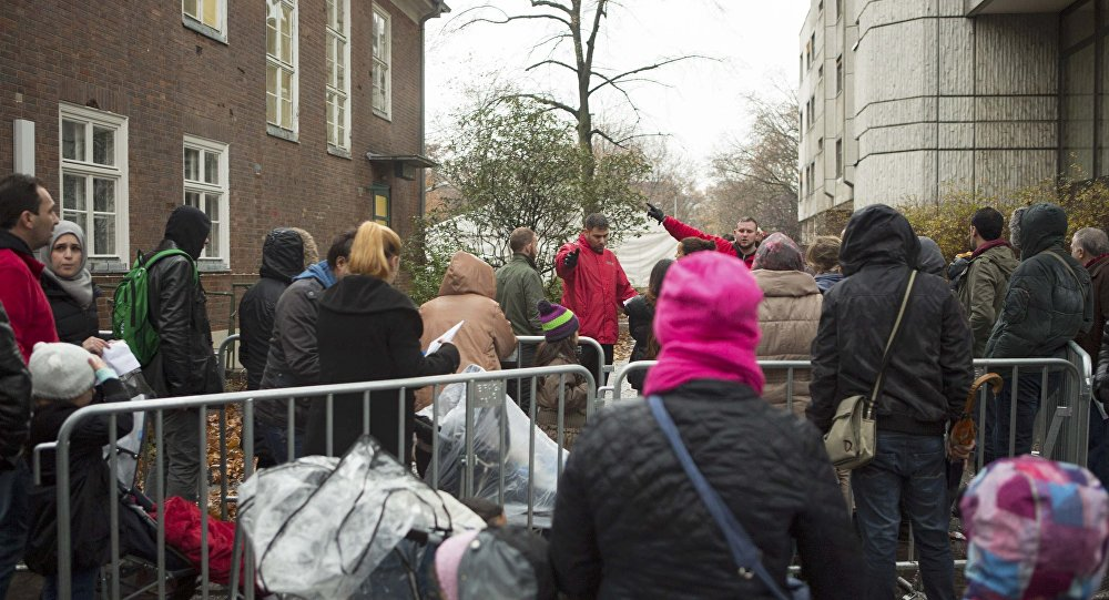 Migrants queue at the compound outside the Berlin Office of Health and Social Affairs (LAGESO) waiting to register in Berlin, Germany, November 17, 2015