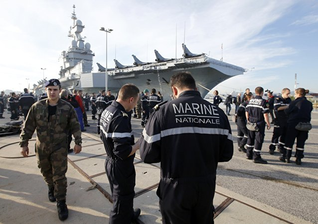 French Navy crew members walk on the docks in front of the French nuclear-powered aircraft carrier Charles de Gaulle before its departure from the naval base of Toulon, France, November 18, 2015