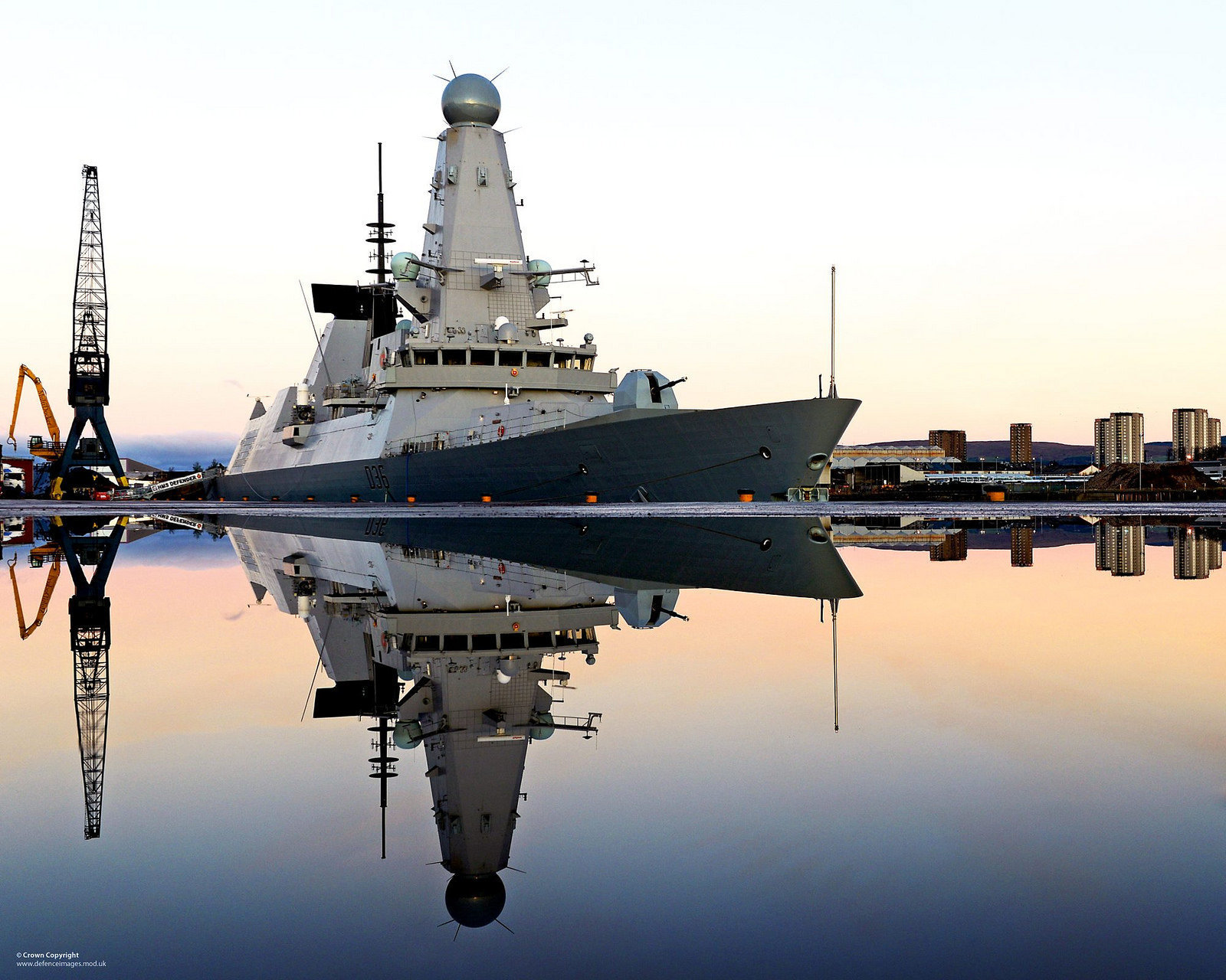 Royal Navy Type 45 destroyer HMS Defender is mirrored in water following a downpour on the dockside
