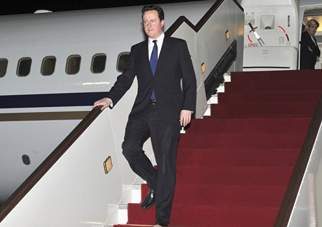 British Prime Minister David Cameron walking down the stairs of an airplane