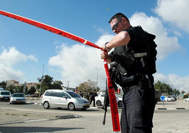 An Israeli police officer holds police tape.
