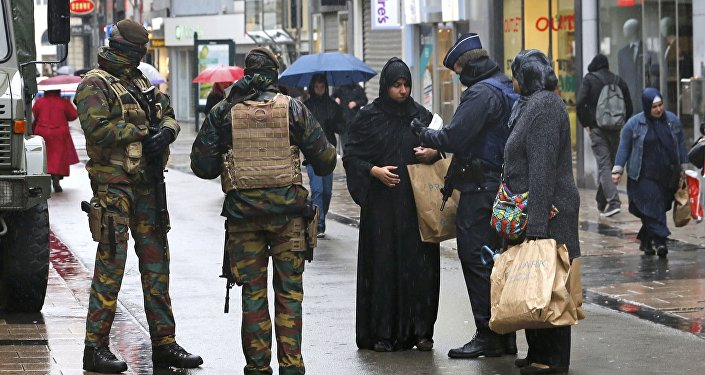 Belgian soldiers and a police officer control the documents of a woman in a shopping street in central Brussels, November 21, 2015, after security was tightened in Belgium following the fatal attacks in Paris